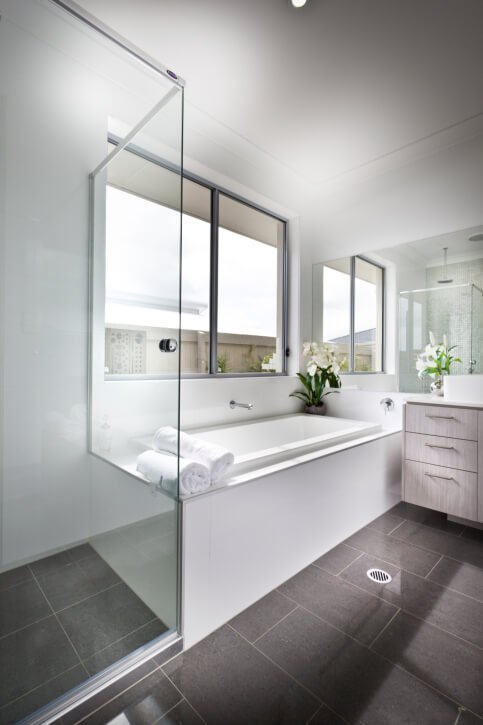This bright bathroom features large format brown tile flooring and white walls and bath surround. Light wood cabinetry on the vanity adds a layer of detail, as does glass enclosed shower.