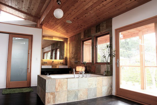 This bathroom mixes modern and rustic elements, for a unique look. Dark hardwood flooring, stone brick bath surround, and bright natural wood paneling create an interesting mix of textures.