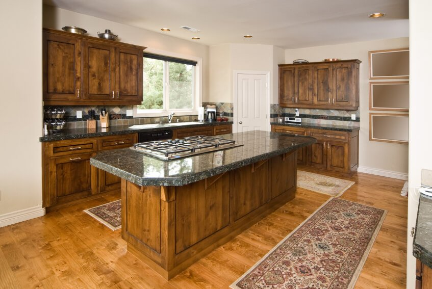 The gorgeous natural wood of these dark cabinets complements the textures in the lighter wood flooring and give this a rustic, cottage feel without taking away from this classy kitchen.