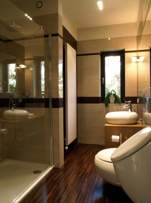 This richly textured bathroom features slim-panel hardwood flooring in a dark, rich tone, beneath textured beige walls and a light wood vanity with vessel sink. Glass enclosed shower and modern conveniences create a fresh look.