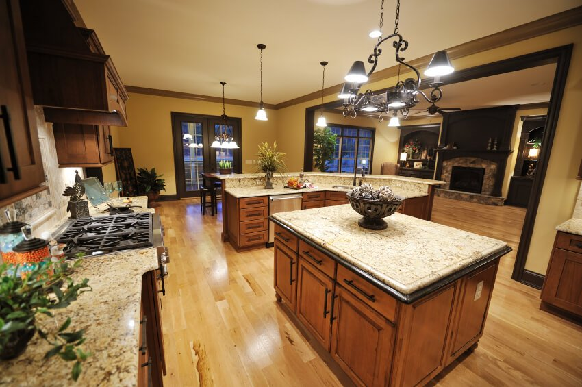 This marvelous kitchen features beautiful granite countertops, warm wood cabinets, and a pale wood floor all accentuated by black trim and hardware.