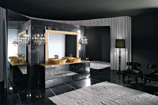 This bespoke bathroom is awash in dark marble, with flooring and central vanity structure in matching black tones. A splash of bright natural hardwood adorns the countertop and vessel sinks, lit by candle style sconces.