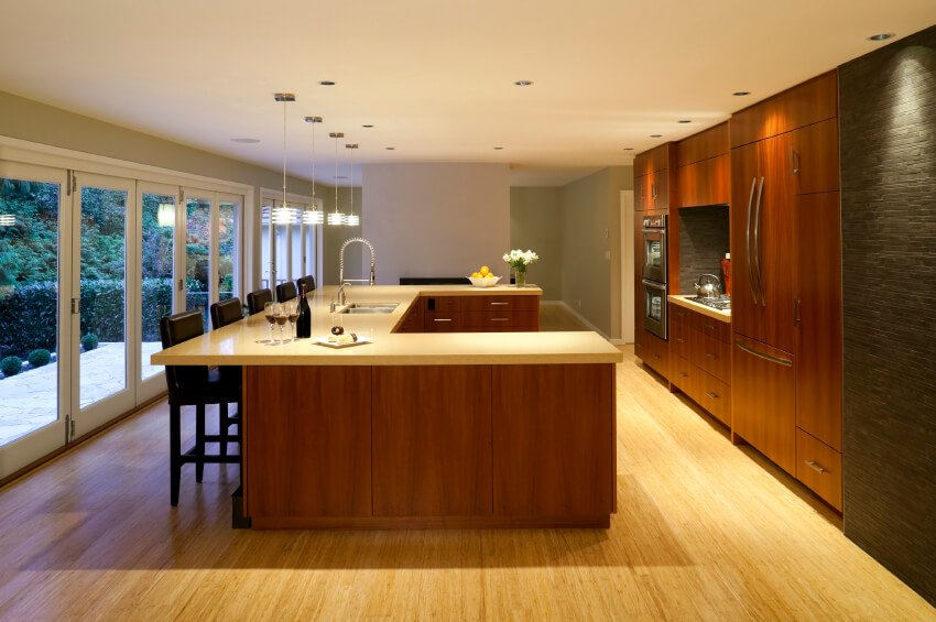 This clean-cut kitchen is brightened by the light wood floor and matching countertops. The warm bronze tones of the cabinetry are highlighted by recessed spotlights in the ceiling. A textured stone accent wall completes the look.
