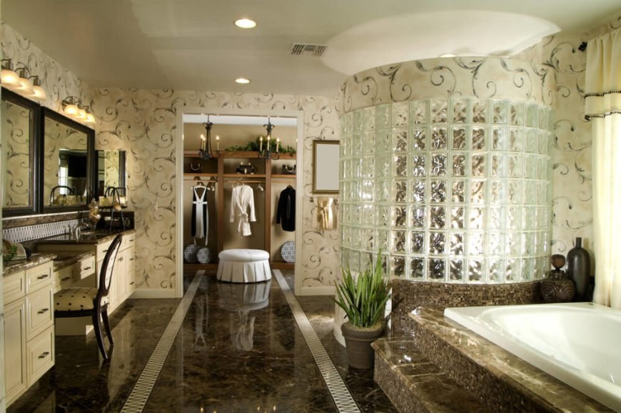 This sprawling luxury bathroom spreads over a rich marble floor with intricate white strip designs. Soaking tub and glass brick enclosed shower at right stand wrapped in micro-tile, while dual vanity at left sports beige cabinetry and more marble on the countertops. A large walk-in closet can be seen at the far end.
