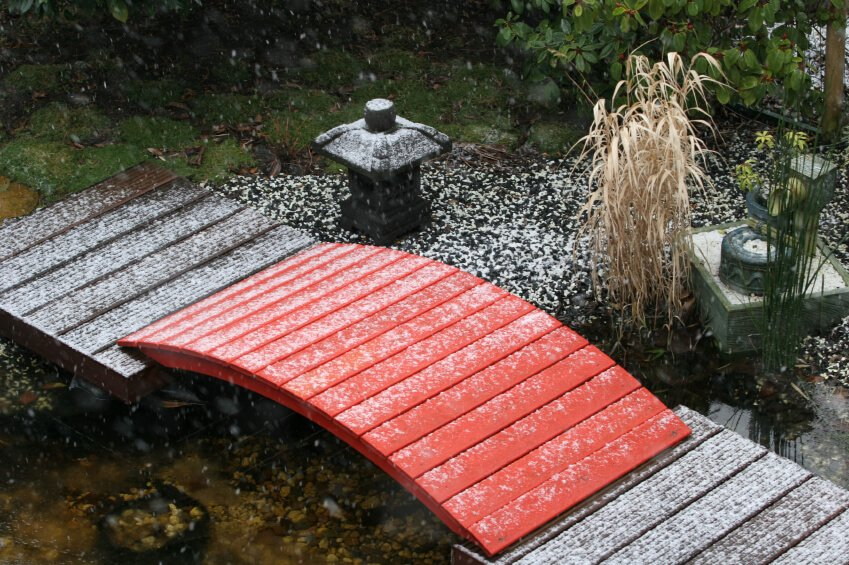 A small red footbridge without railings is caught in a sudden snowstorm. Soft white flakes are piling up on the traditional Japanese stone lantern.