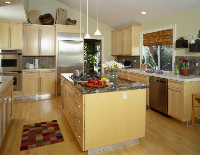 The warm, yellow tone of the wood in this kitchen is offset by the use of stainless steel appliances and brushed nickel hardware. A standout granite countertop on the island adds immense detail.
