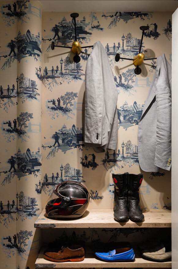 The walk-in closet has more of a rustic tone, with wallpaper that has London scenes printed on it in blue and open shoe shelving.