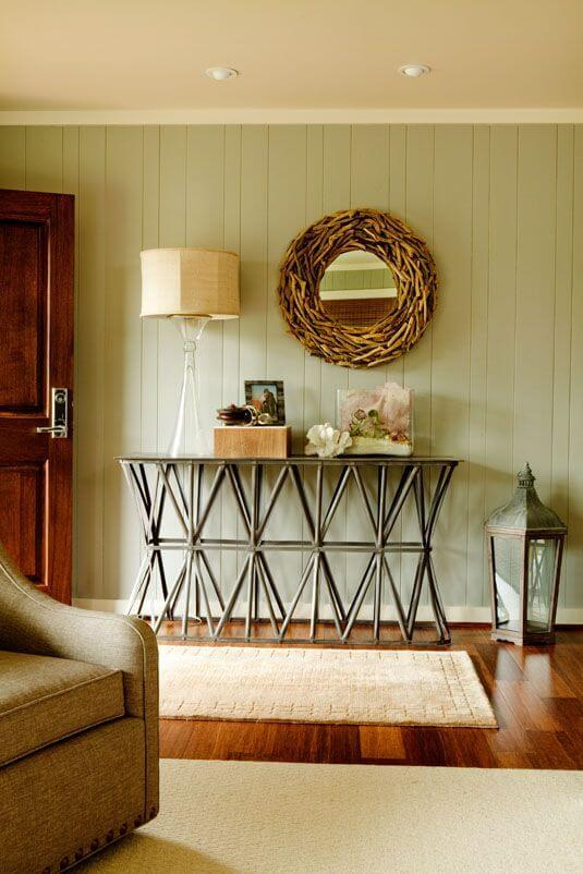 A close up of the table in the entryway, a very casual table with beach accents like shells covering it. To the right is an old lantern. On the wall above is a mirror in a wreath of branches.