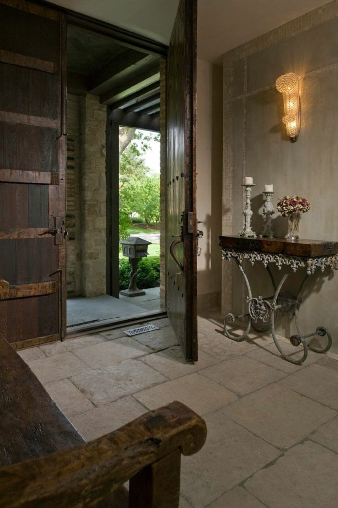 A view of the foyer from near the distressed, rustic bench at the white wrought iron table across the foyer. A mosaic tile border on the walls is a unique touch that adds Old World flavor to the stunning entrance.