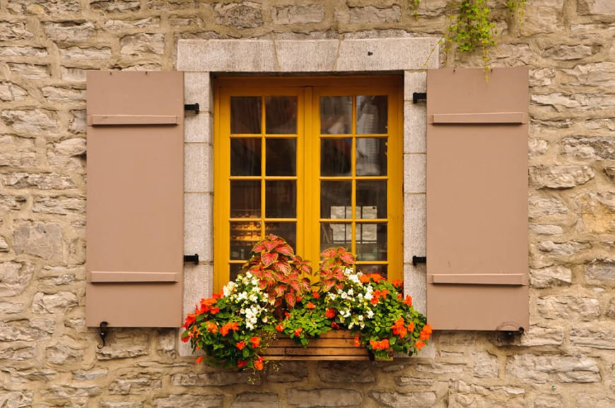 A narrow yellow window in Quebec with a small wooden window box filled with red and white flora.