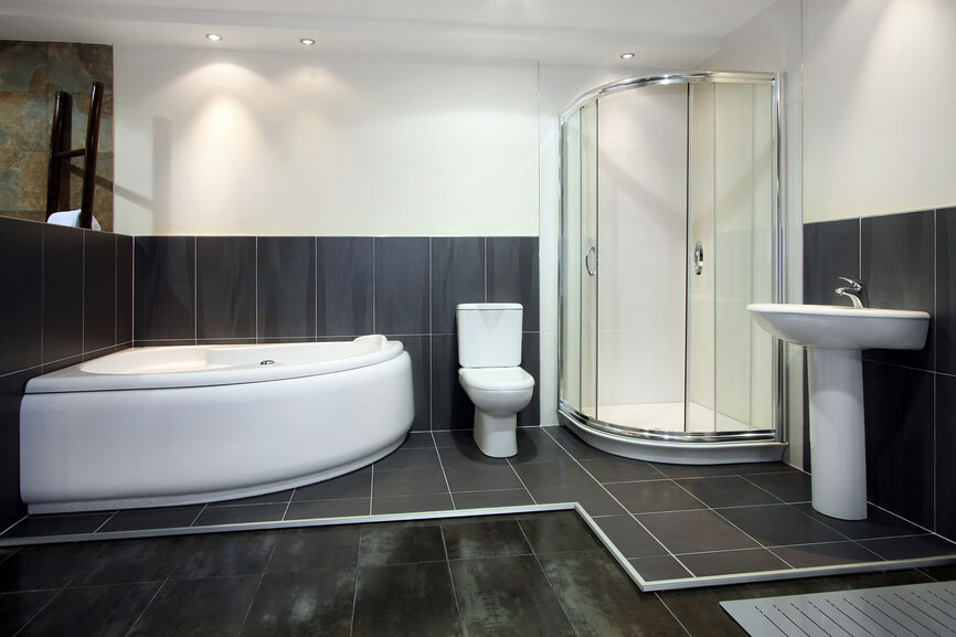 This high contrast bathroom features both large format worn black floor tiling and a raised black tile surface surrounding the bath area. Curved glass enclosed shower fills the corner, across from corner mounted soaking tub in white.