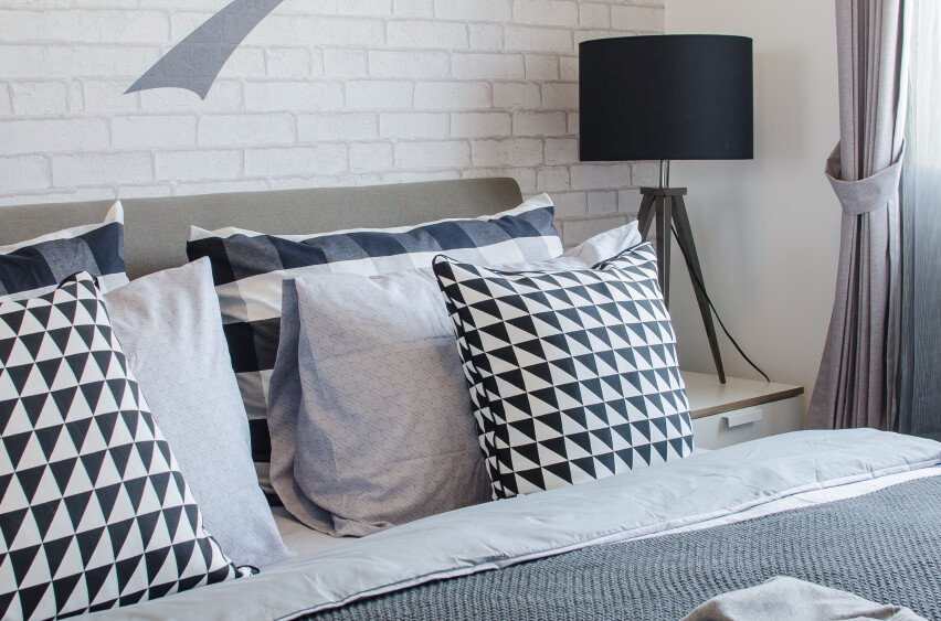 Black and white checked throw pillows stand out against the simple backdrop of the white painted brick wall. Variations in gradient and patterns add interest and appeal to a space that might otherwise be bland.