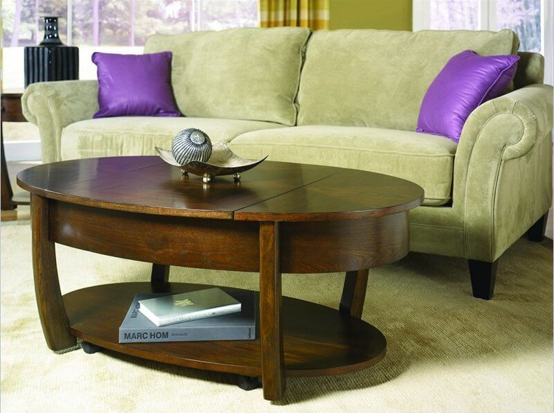 This rich, dark wood two-tiered coffee table hides an expansive storage system. The central and side pieces of the table top can lift to reveal ample storage beneath.