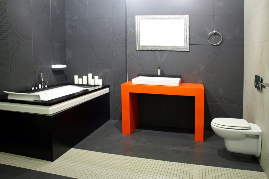 This ultra-modern bathroom features a burst of color over dark grey flooring and walls, with an orange vanity at center. Large soaking tub is framed in black and white, for further contrast and detail.