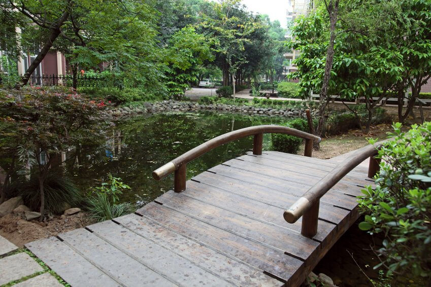 The transition between path and bridge is utterly seamless over this still, reflective pond.