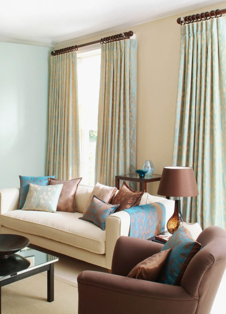 A delicate pattern in the curtains that matches accent pieces in the room is a great way to add visual interest and tie solid pieces into an overall design scheme.