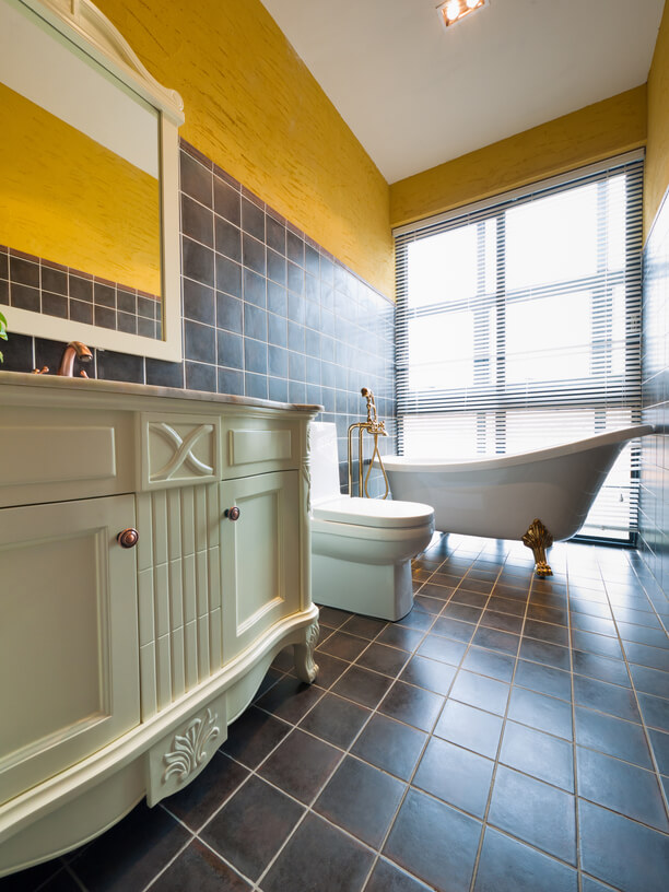 This traditional bathroom features dark brown tile flooring and partial wall covering. Ornate vanity topped with marble, plus white clawfoot tub with gold feet, add to the vintage luxury.