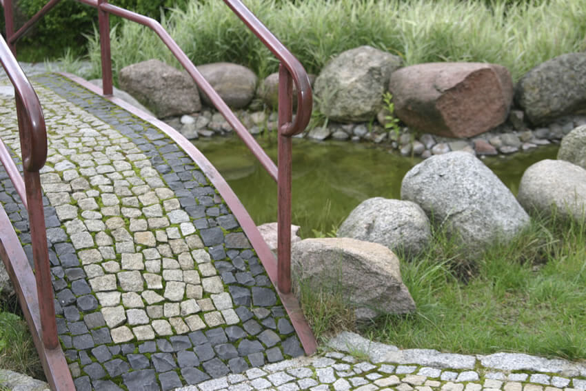 Simple light and dark stones are set in a mosaic pattern along this bridge. The railings are a light burgundy wrought iron, and the spaces between each stone are filled with moss.
