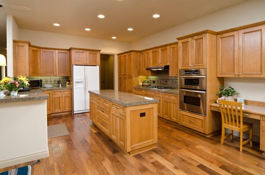 This beautiful floor varies in shades and colors, bringing in hints of the cabinetry. The bright white half wall around the left side of the counter space helps to brighten the room considerably.