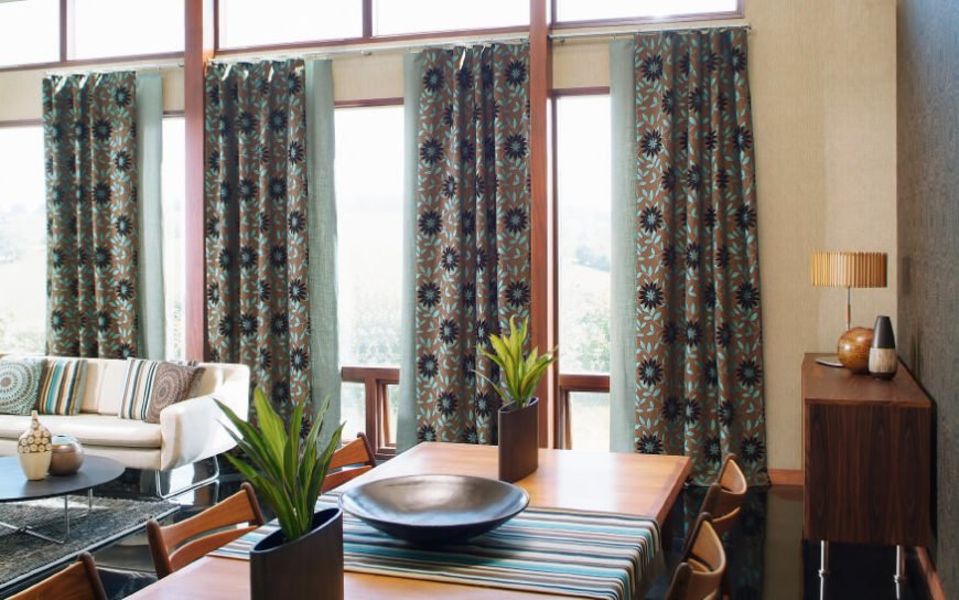 In this case, the bold floral pattern of these turquoise and brown curtains pulls color from the other patterns, creating a layered effect.