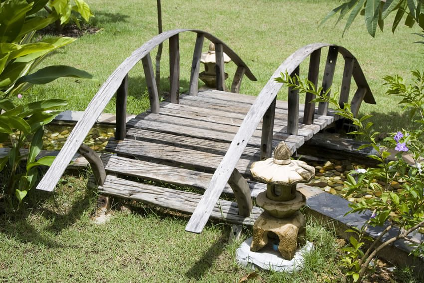 The simple, rustic design of this Japanese bridge invokes the image of a wagon wheel. The bridge crosses a man-made pebble-bottom stream.