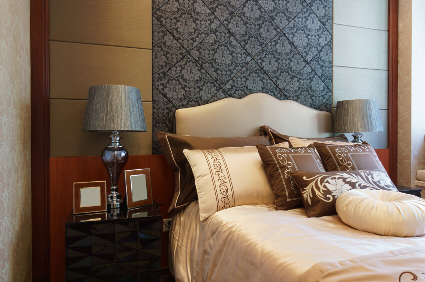 Cream, ivory, and chocolate browns envelop the room, with an intricate black accent panel overseeing the space. An arrangement of delicately embroidered throw pillows grace this lovely bedroom, and offer a richness that would be lacking in their absence.