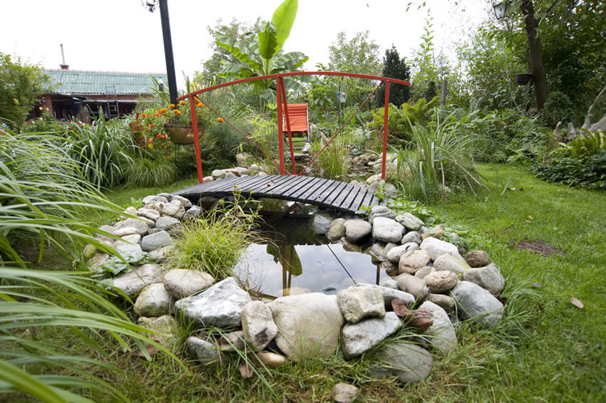 A single red railing stretches on one side of this simple wooden bridge. The bridge crosses a small man-made stream and pond.