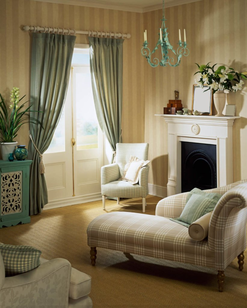 This living room has a more toned down design, with soft plaids and dusky blues. The curtains frame French doors.