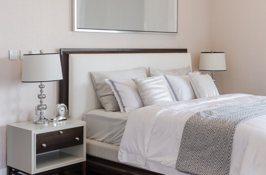 This soft room is crisp and classic. Neutral grays and beige hues offer a restful and attractive sleeping area, while the pillow arrangement features complementary light colors in a pleasing manner. Lightly patterned square accent pillows are placed against white pillows with dark trim for contrast, while large gray sleeping pillows rest against the coordinating padded headboard.