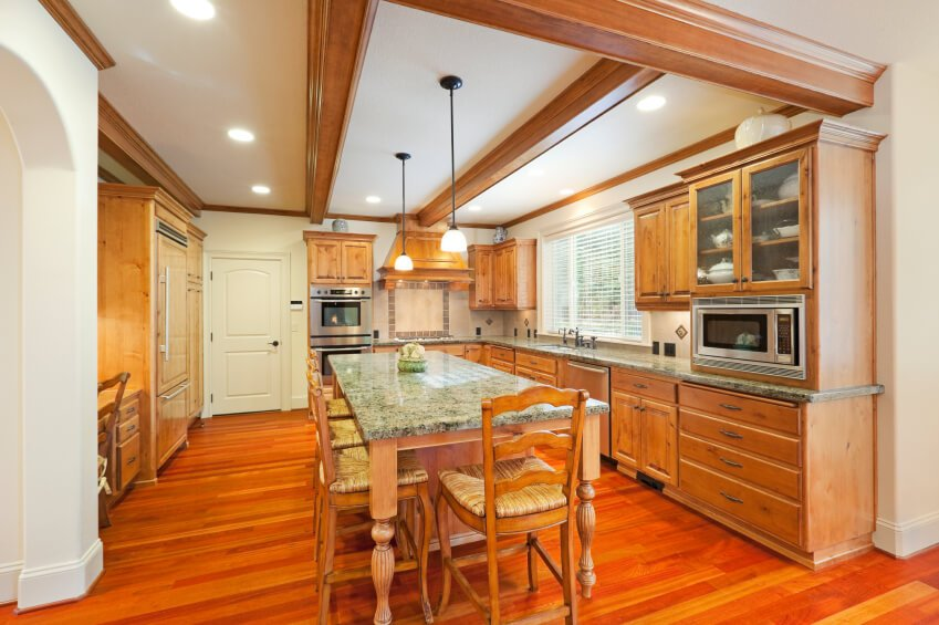 This narrow kitchen uses exposed beams to make it appear longer while the warm wood flooring runs across the room to create opposition and interest. The beautiful green granite counters add a lovely pop of color.
