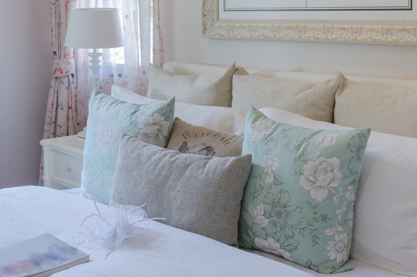 Light, cheerful, and extraordinarily feminine, this bedroom employs a variety of materials and patterns in a shabby chic style that is not shabby at all. The understated neutrals allow light pastels to take center stage and bring a subtle pop of color to the space.