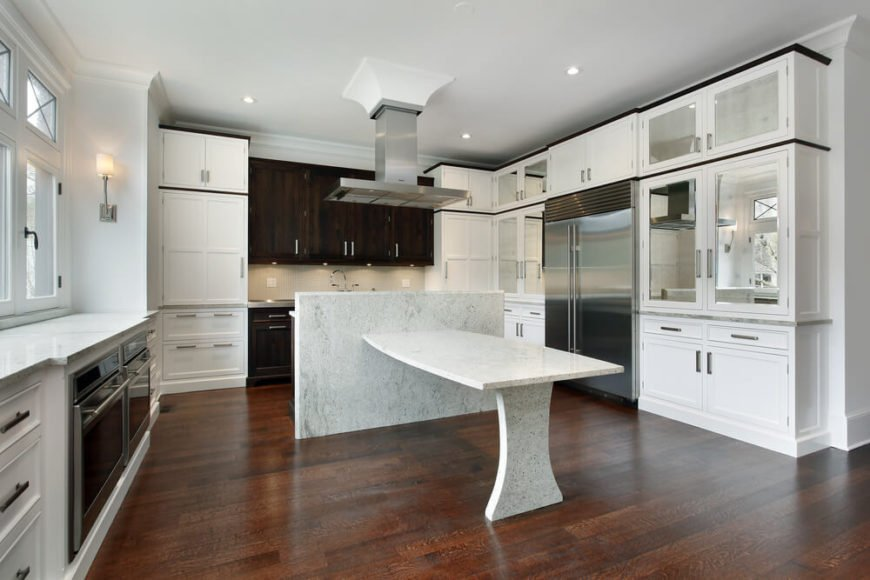 This unique kitchen has a granite island that extends into a table and preparation space. The beautiful dark wooden floor highlights the various bright whites and metallic colors of this kitchen.