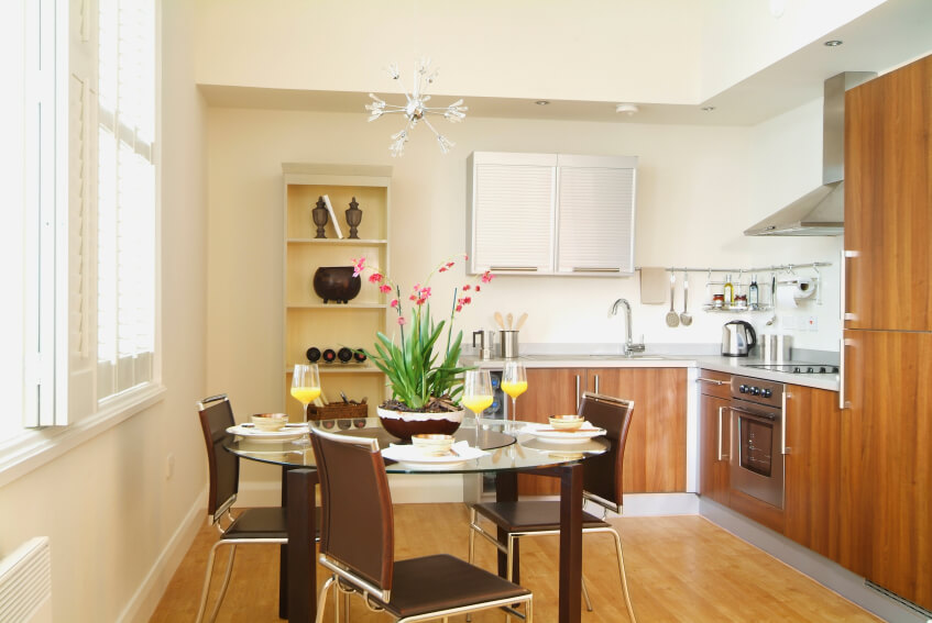 This small kitchen utilizes its space well with lots of white to make it appear larger that it is. The chocolate brown of the table and chairs complements the beautiful cabinets.