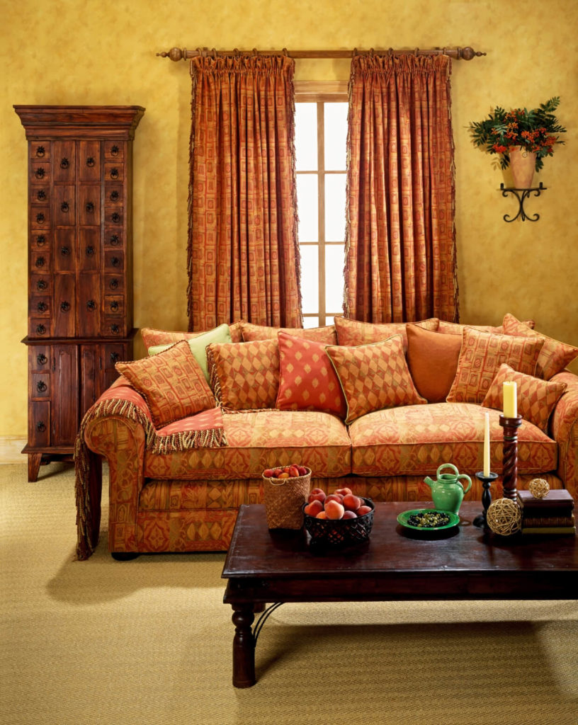 A subtle geometric pattern in the curtains complements the array of patterns on the sofa and throw pillows.