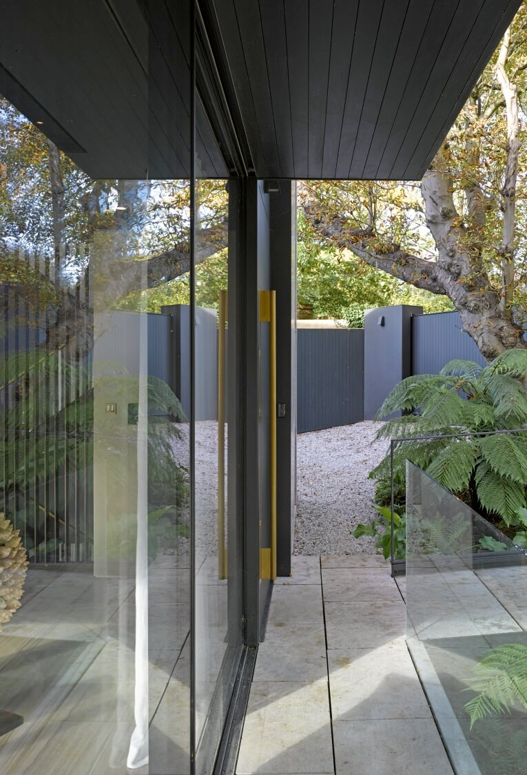 The front entrance and surrounding glazing is wrapped by a thin veranda, framed in glass railing.