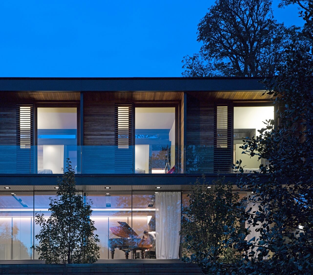 The two floors visible here achieve transparency with full height glazing, while the upper level uses extensive hardwood paneling for privacy in the bedroom spaces.