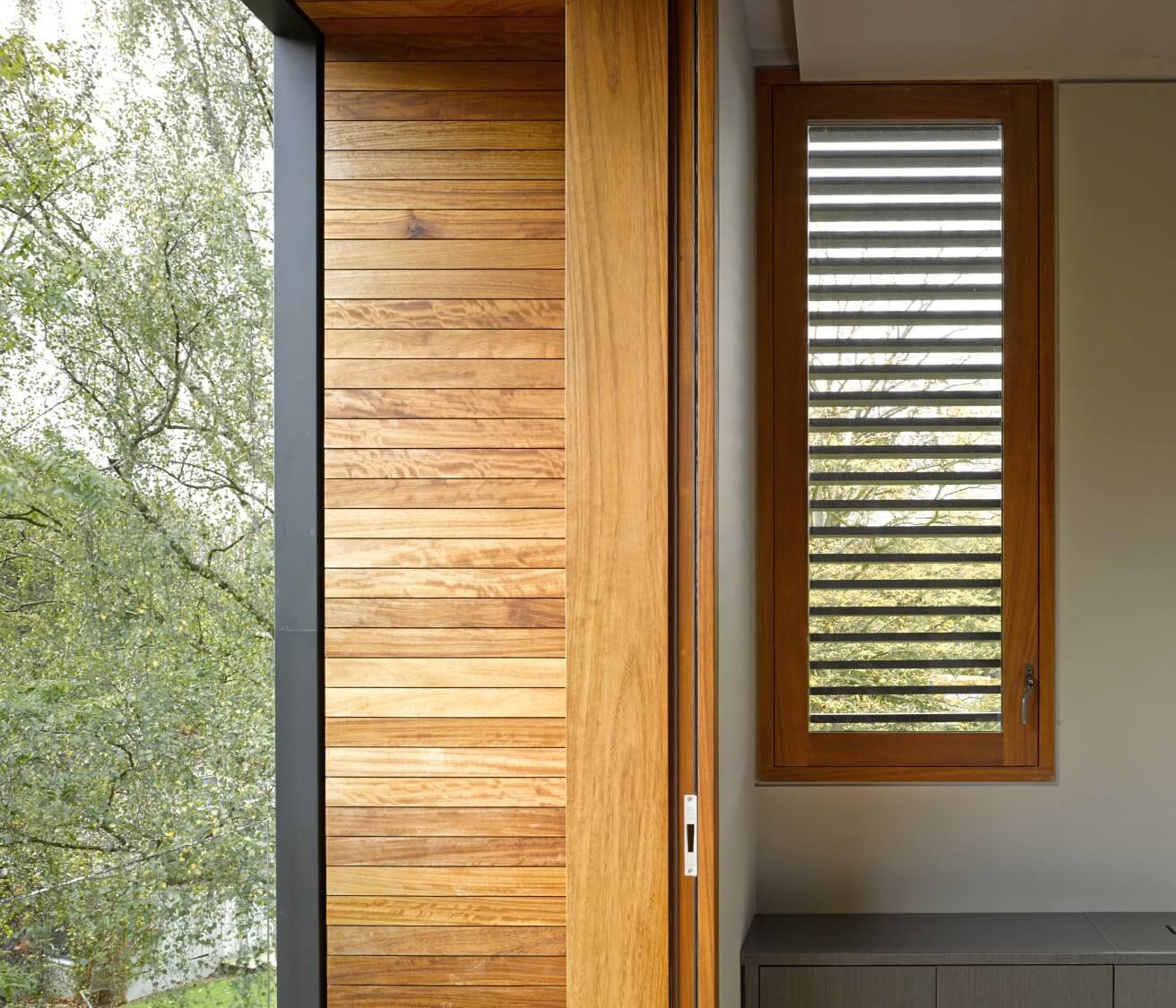 Here we see one of the upper level rooms open to the environment by pocket door, leading to the wood wrapped balcony.