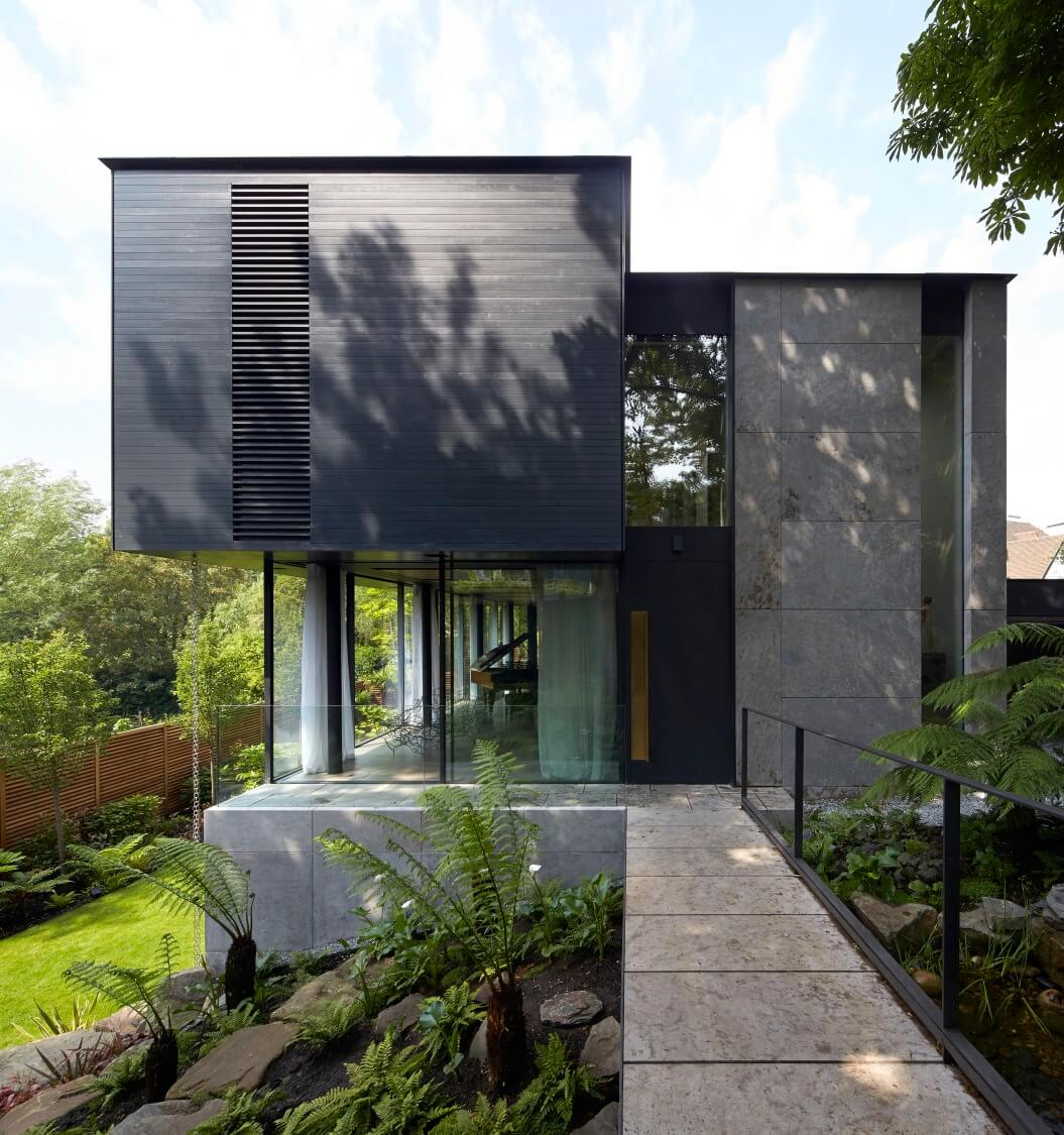 The slim metal and stone bridge allows the home to be virtually wrapped in greenery and natural stones. Here we see the main entrance standing next to full height glazing, revealing the interior on approach.