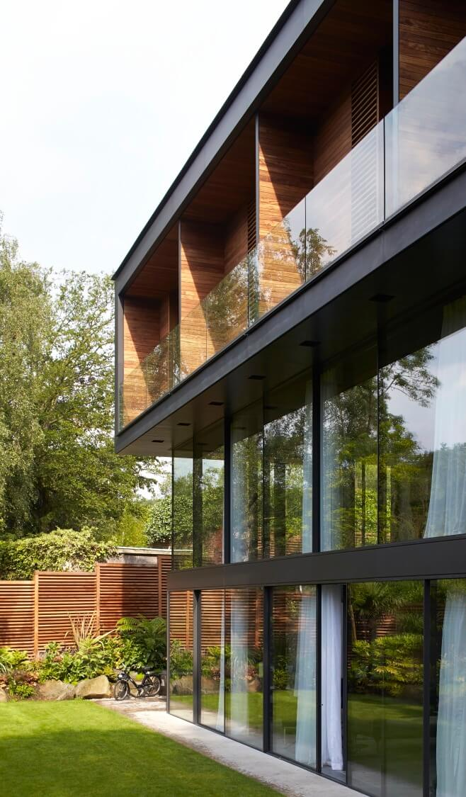 On the garden side of the home, full height glazing covers the large, double height first floor exterior. Above, we see the segmented balcony wrapped in rich natural wood.