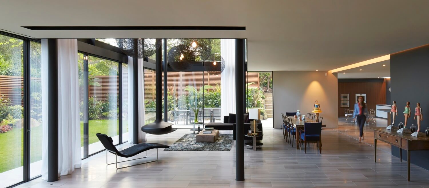Beneath the upper floor, the expansive open-plan space includes a large dining area and flows into a kitchen space, seen at right.