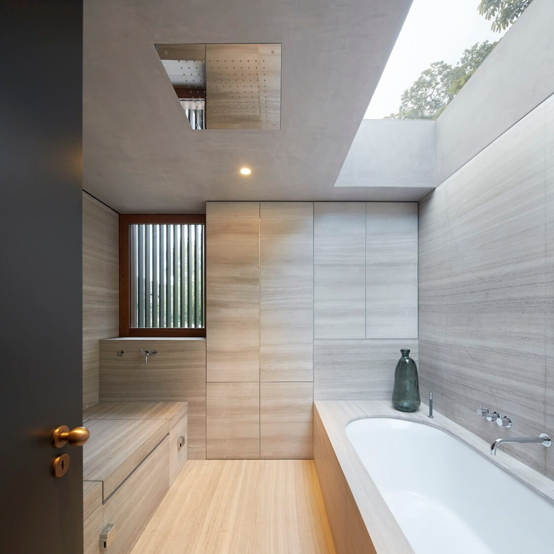 Bathroom is awash in rich marble from the floor up, glowing in natural light via skylight. The design includes a rainfall shower head at center, for a completely open shower design.