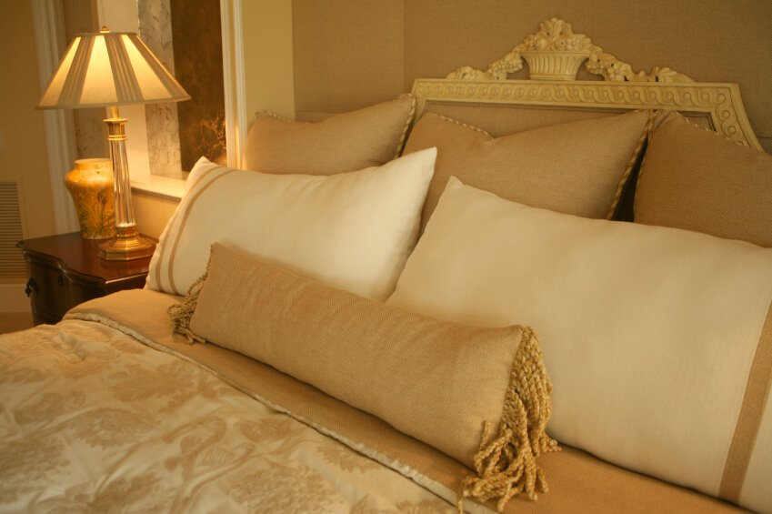 The gold and ivory design scheme of this room and the intricate attention to detail make this space exceptionally luxurious. An oblong gold throw pillow with a soft fringe sits against ivory and gold trimmed pillows and large square accent pillows in the rear. An opulent headboard acts as a frame, while the delicate gold and cream duvet cover ties everything together.