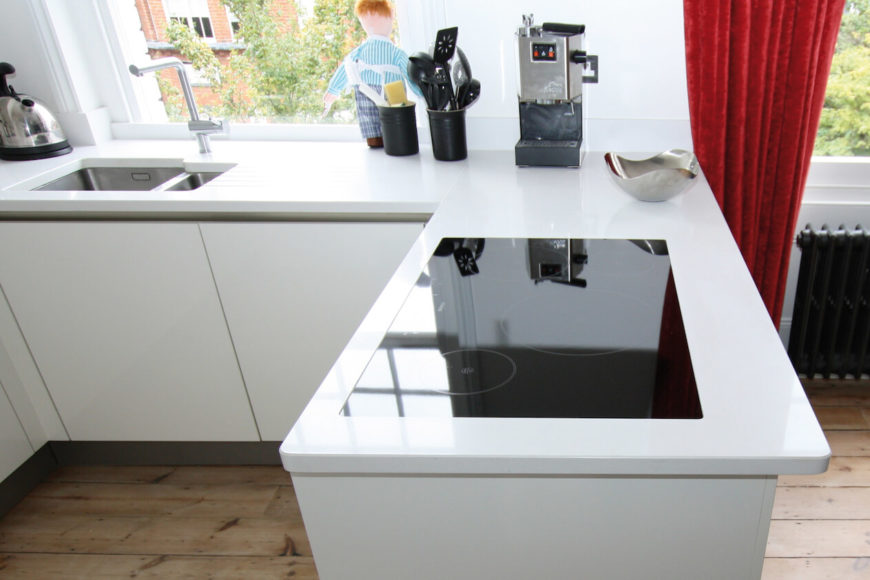 The sleek white countertops add an interesting contrast around the flat, modern cooktop. Natural toned hardwood flooring makes the white really pop.