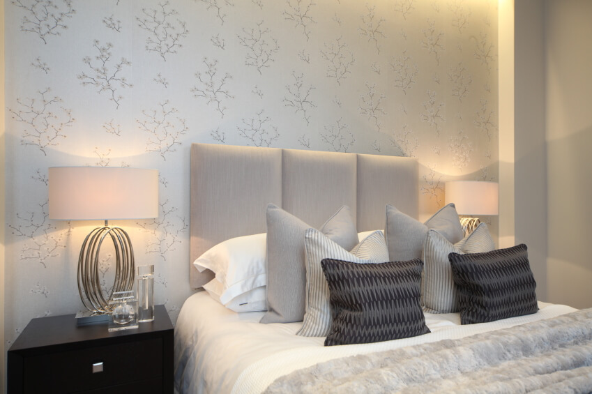 This phenomenal bedroom features delicately patterned wallpaper in cream and beige, tying the neutral room together with quiet determination. Modern metal lamps grace ebony end tables, while a wonderful arrangement of throw and accent pillows sit upon the bed.