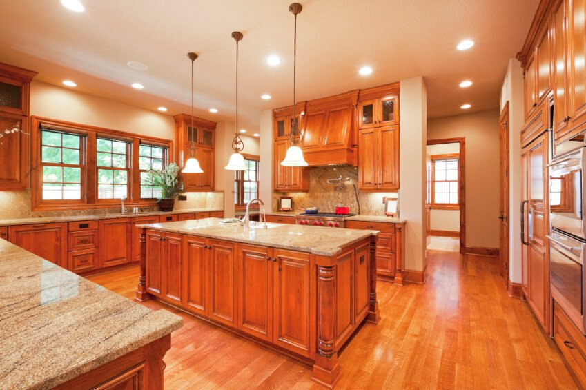 The light wood floors of this kitchen brighten the already warm space created by the cabinetry. The space appears larger with high cabinets, bright lights, and lots of windows.
