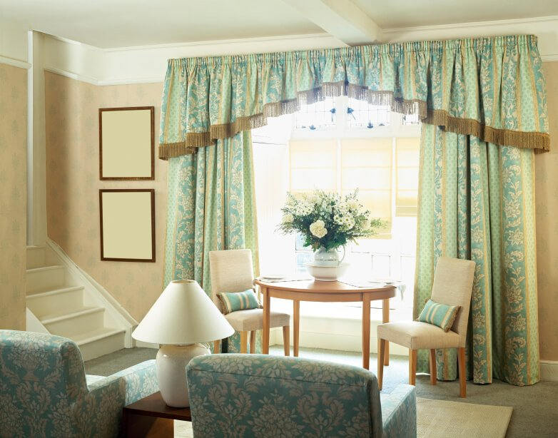 Heavy traditional curtains in a light blue frame the bay windows behind a small table and armless chairs.