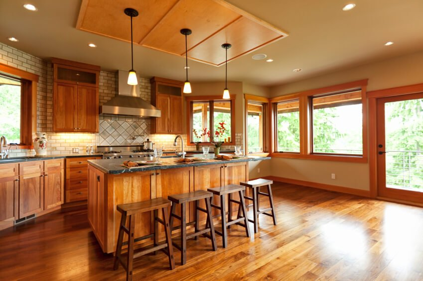 These beautifully textured wood floors add to the cabinets and wood trim around the room. The use of sage green subway tiles as a backsplash accents the veins of pale green in the granite countertops.