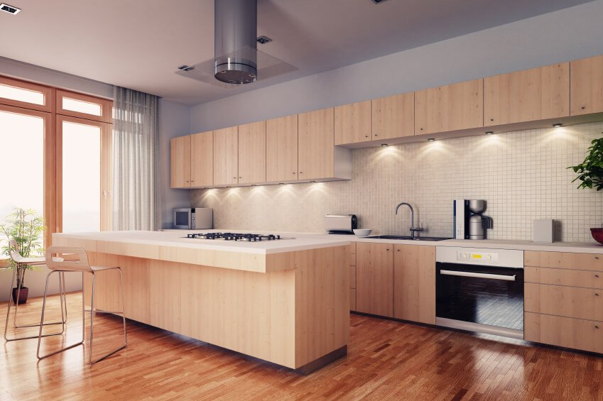 This soft kitchen is brought color and interest by the warm reds of the wood floor, complementing the calm beauty of this minimalist space.