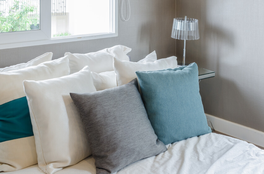 White accent pillows support a soft gray and blue pair of pillows upon soft bedding. Gray walls offer a fine canvas, and a delicate glass lamp brings additional interest to this quiet space.