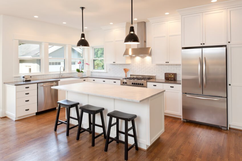 This beautiful, warm wood floor adds color and interest to this lovely cool white kitchen. The large island features ample space for in-kitchen dining.